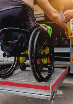 Man in wheelchair using accessible vehicle with lift mechanism