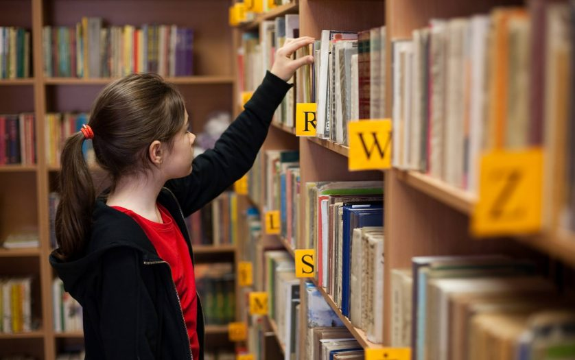 Young girl in library looking for books