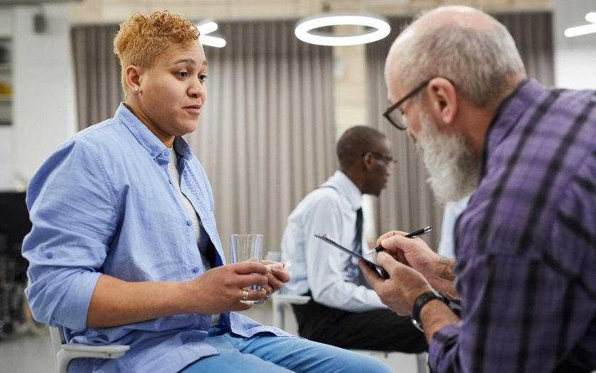 Side view portrait of mature man consulting masculine woman in therapy session