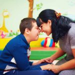 portrait of cheerful mother and her beloved son with disability