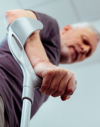 Selective focus of a male hand holding crutches while using it for walking