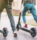 Close up of people using electric scooter in street