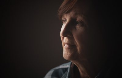 Close-up portrait of senior woman with dementia who is looking through window.