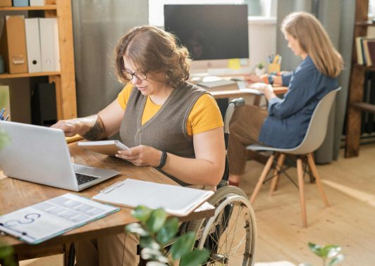 Young woman in wheelchair in front of laptop and networking while her colleague working behind