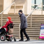 Person in wheelchair with a man walk into Metro Convention Centre vaccination centre to receive their COVID-19 vaccine.