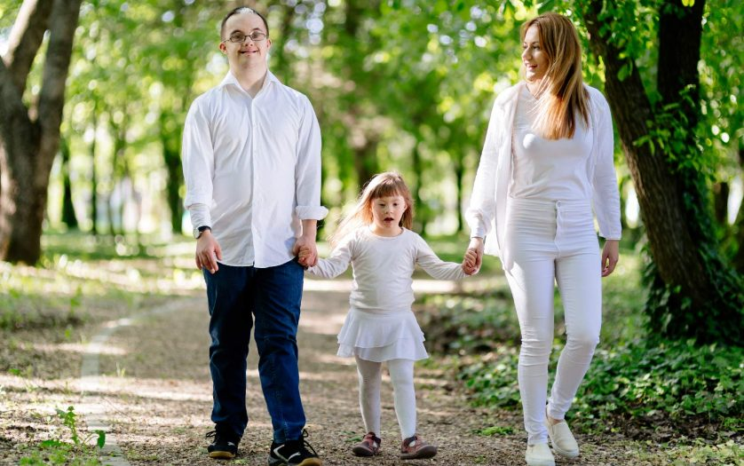Parents with daughter with Down syndrome, walking in nature