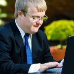 Close up portrait of businessman with down syndrome working.