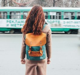 Young woman curly red head girl with backpack in front of tram at the city street