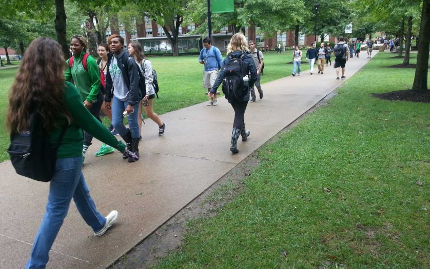 A campus sidewalk is filled with male and female students walking to and from class
