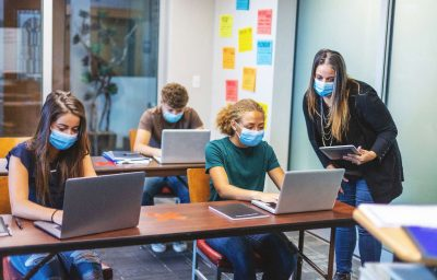 High School Students wearing masks and using computers in a classroom with social distancing measures