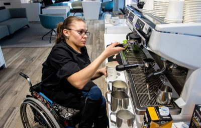 Wheelchair disabled person works as a barista in an inclusive coffee shop.