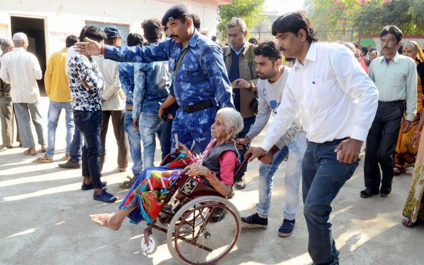 people helping an old lady going to vote in India