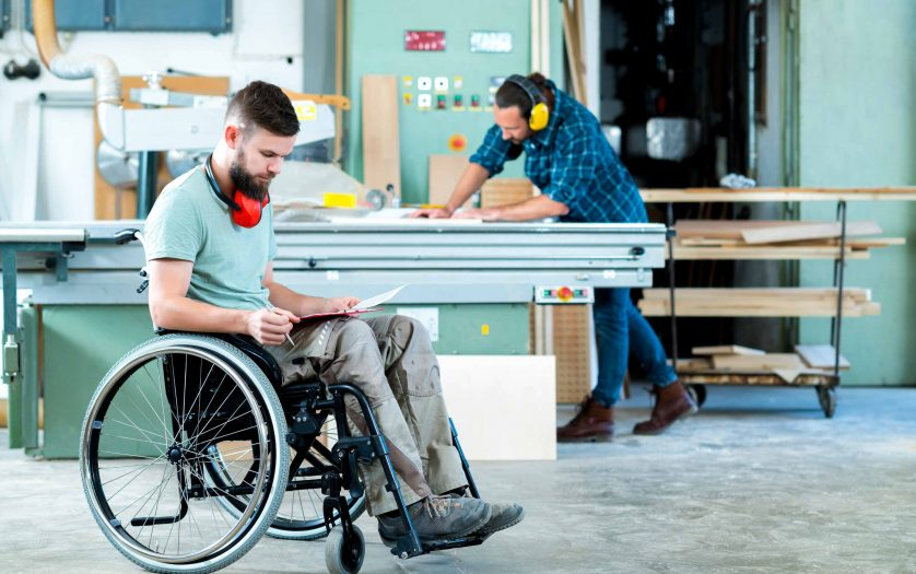 Worker in wheelchair in a carpenter`s workshop with his colleague