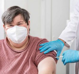 woman with disability is getting a vaccination from a male doctor