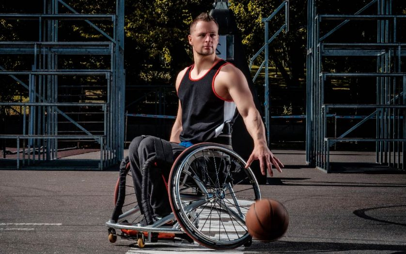 Basketball player in a wheelchair plays on an open gaming ground.