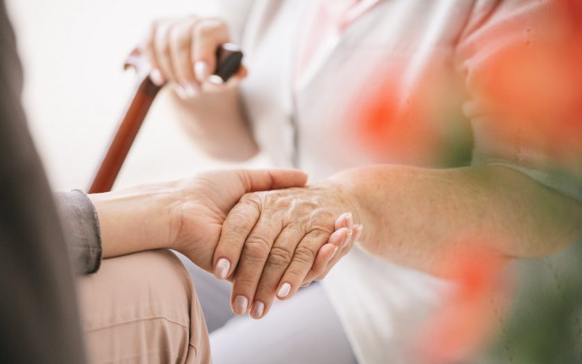 Close-up of young caregiver holding older woman's hand