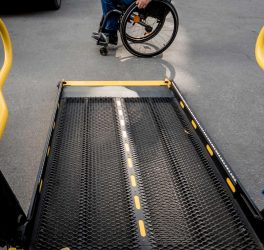A man in a wheelchair moves to the lift of an accessible bus