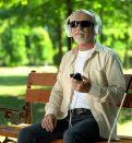 Blind man wearing earphones listening audiobook