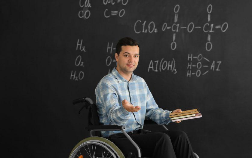 Male teacher with books in wheelchair near chalkboard