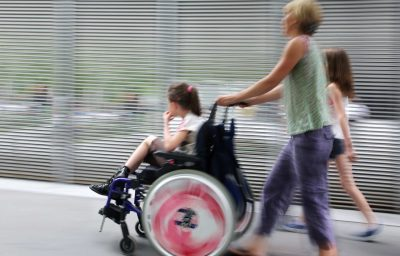 Disabled child in a wheelchair on a city street with family