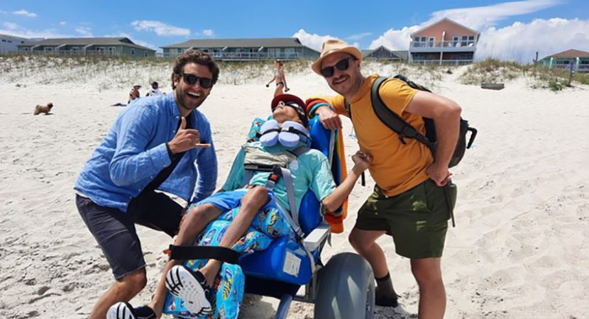 A wheelchair user with smiling people looking at camera outdoor