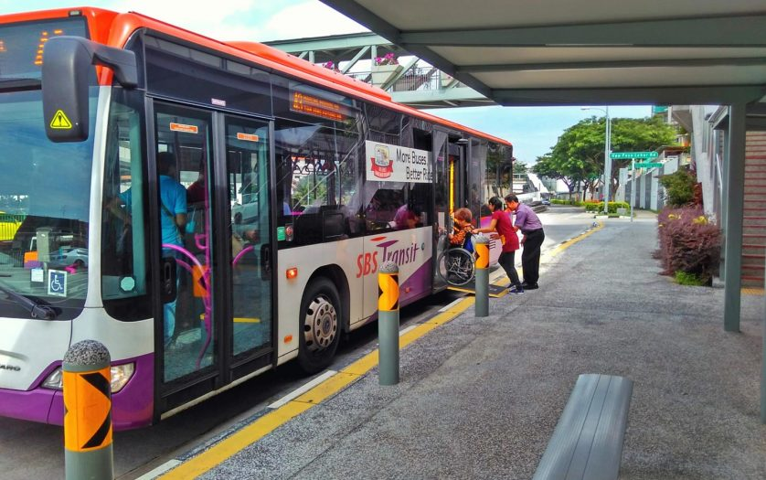 A bus driver lowers the ramp at the rear door for the helper to push a wheelchair bound passenger up onto the bus
