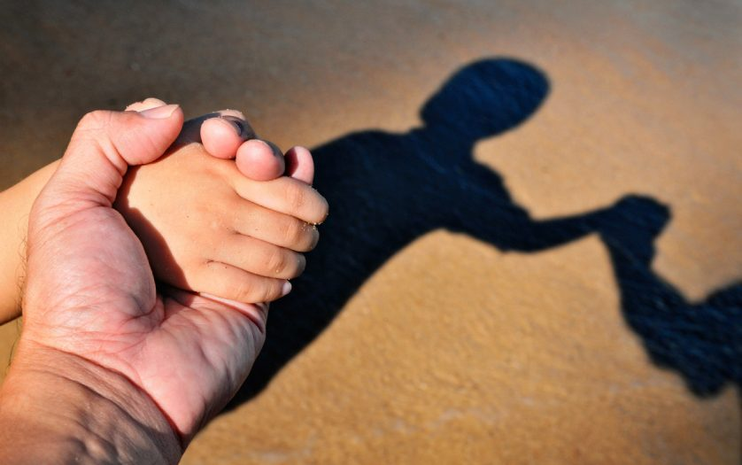 Closeup of father and kid holding hands with their shadows in brown sand background.