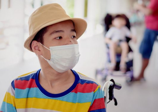 child on wheelchair wearing a protection mask