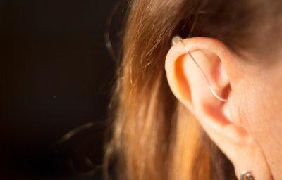 Deaf lady wearing modern digital high technology hearing aid in ear.