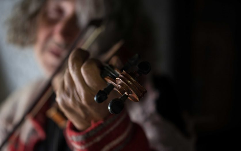 Close up of man playing music on a classical violin indoors.
