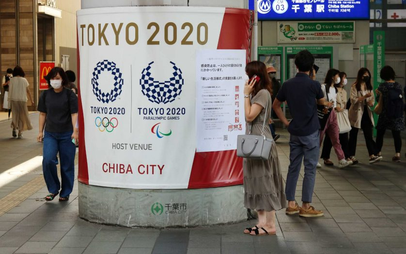A wrapped column in front of Chiba Station, Japan with Tokyo Olympics & Paralympics logos & a poster with advice on coronaviurs safety measures. People wear face masks.