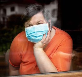 disabled woman with surgical mask looking out at window