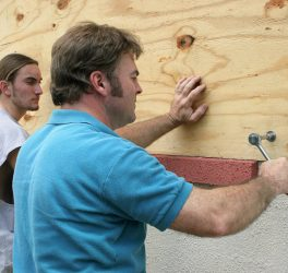 A father & son preparing for a hurricane by putting plywood over the windows