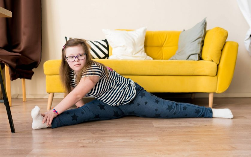 teenager girl with Down syndrome sitting on twine on the floor at home