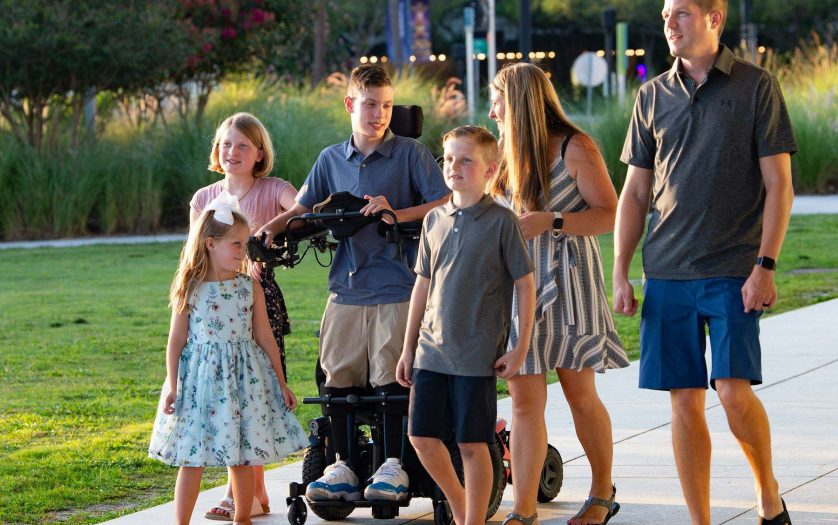 Boy using standing wheelchair with his family outdoor