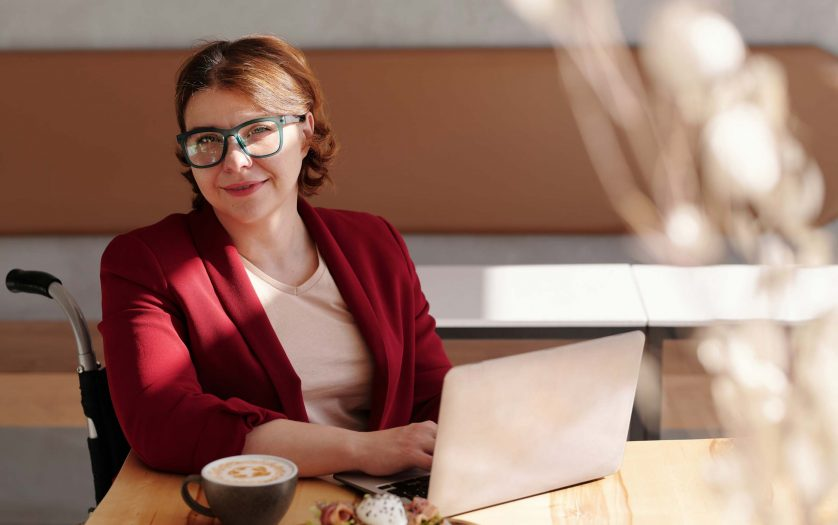 Woman with disability in Red Blazer Wearing Black Framed Eyeglasses